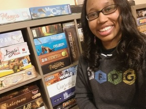 Kellye of Variant Hex in front of board game shelf, wearing an Our Family Plays Games hoodie designed by Beth Sobel